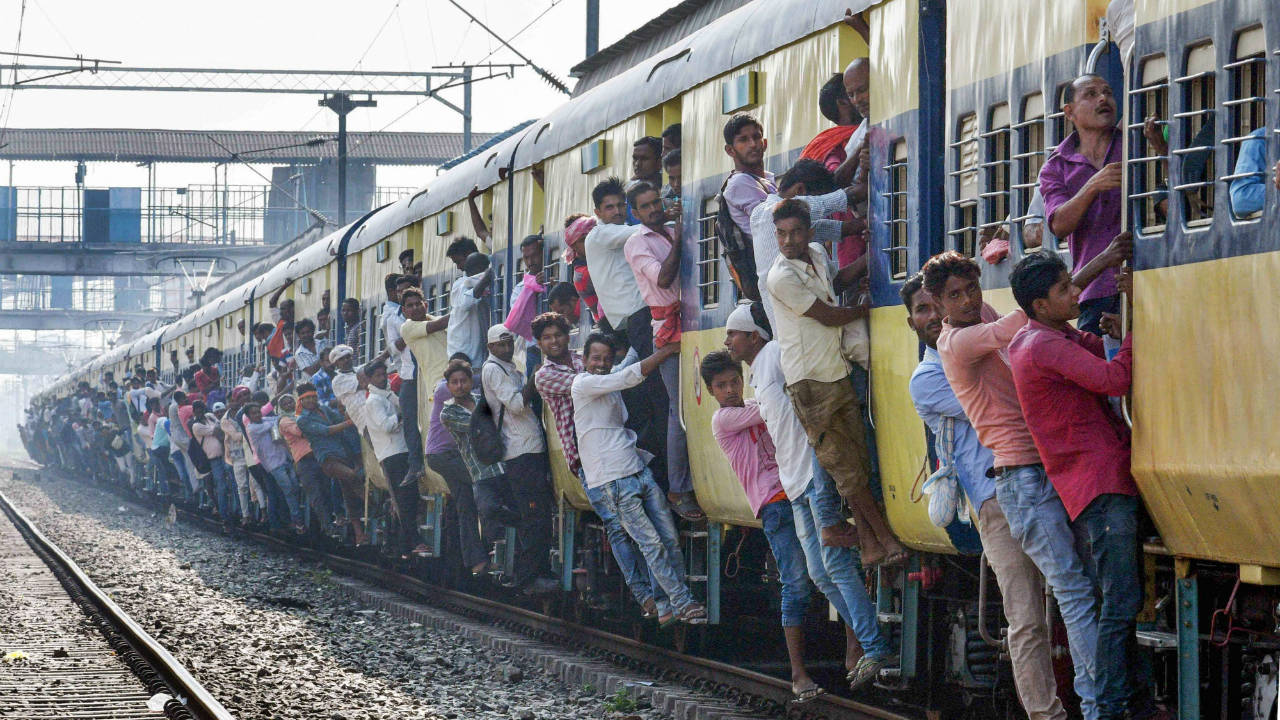 Commuters lean out of an overcrowded local train on the day of Railway Recruitment Board Examination (RRB), in Patna, Bihar. (Image: PTI)