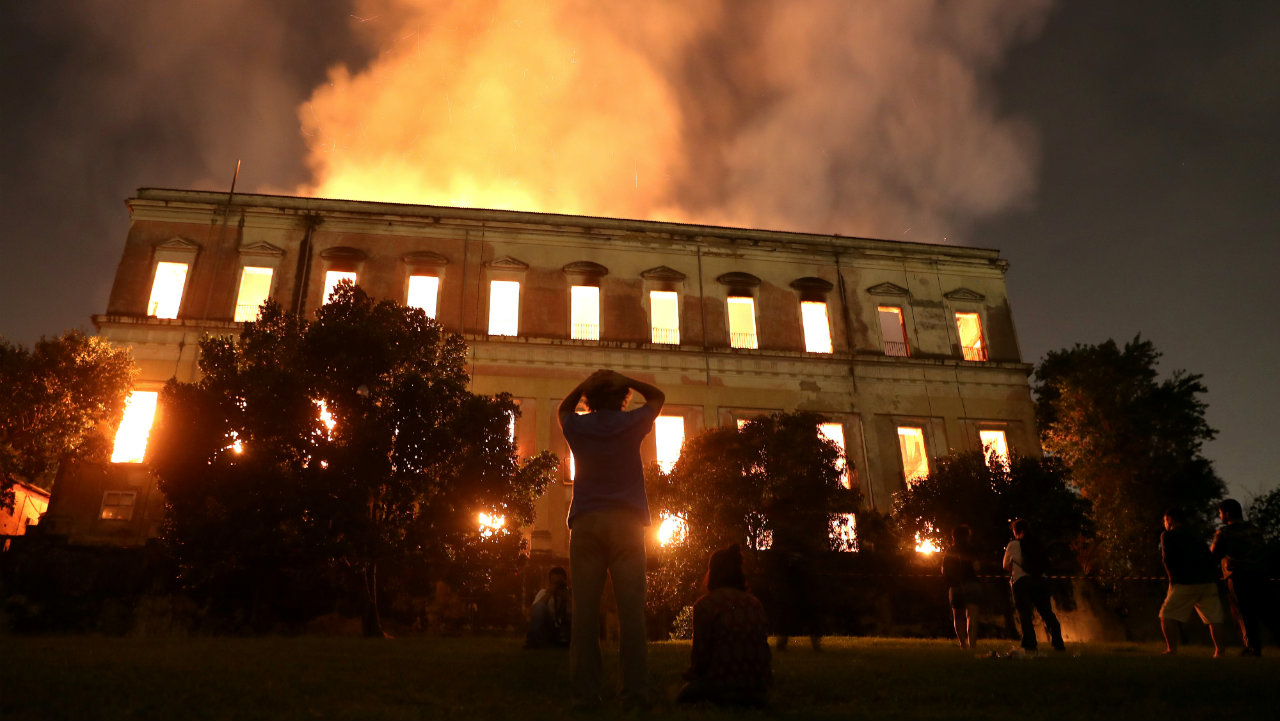 People watch as a fire burns at the 200-year old National Museum of Brazil in Rio de Janeiro, Brazil. The museum houses 20 million items including first fossils found in Brazil. (Image: Reuters)