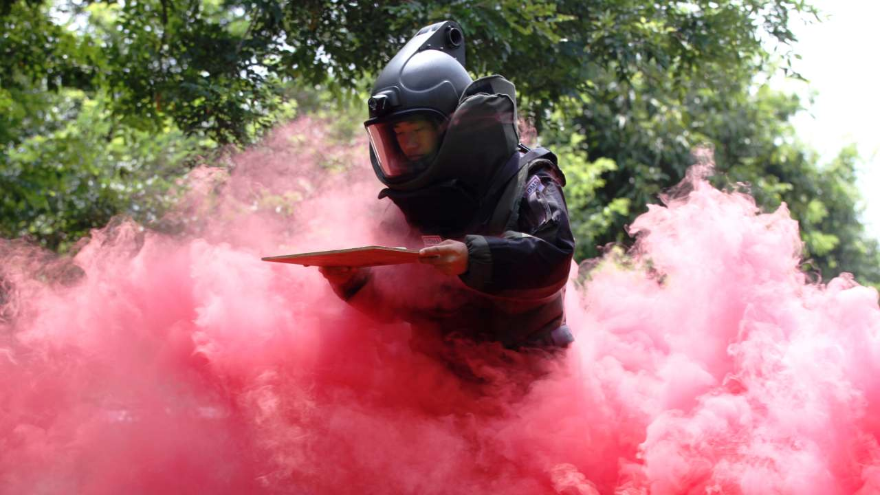 A paramilitary police officer wearing a bomb suit takes part in a bomb disposal drill amid coloured smoke, in Chongzuo, Guangxi Zhuang Autonomous Region, China.(REUTERS)