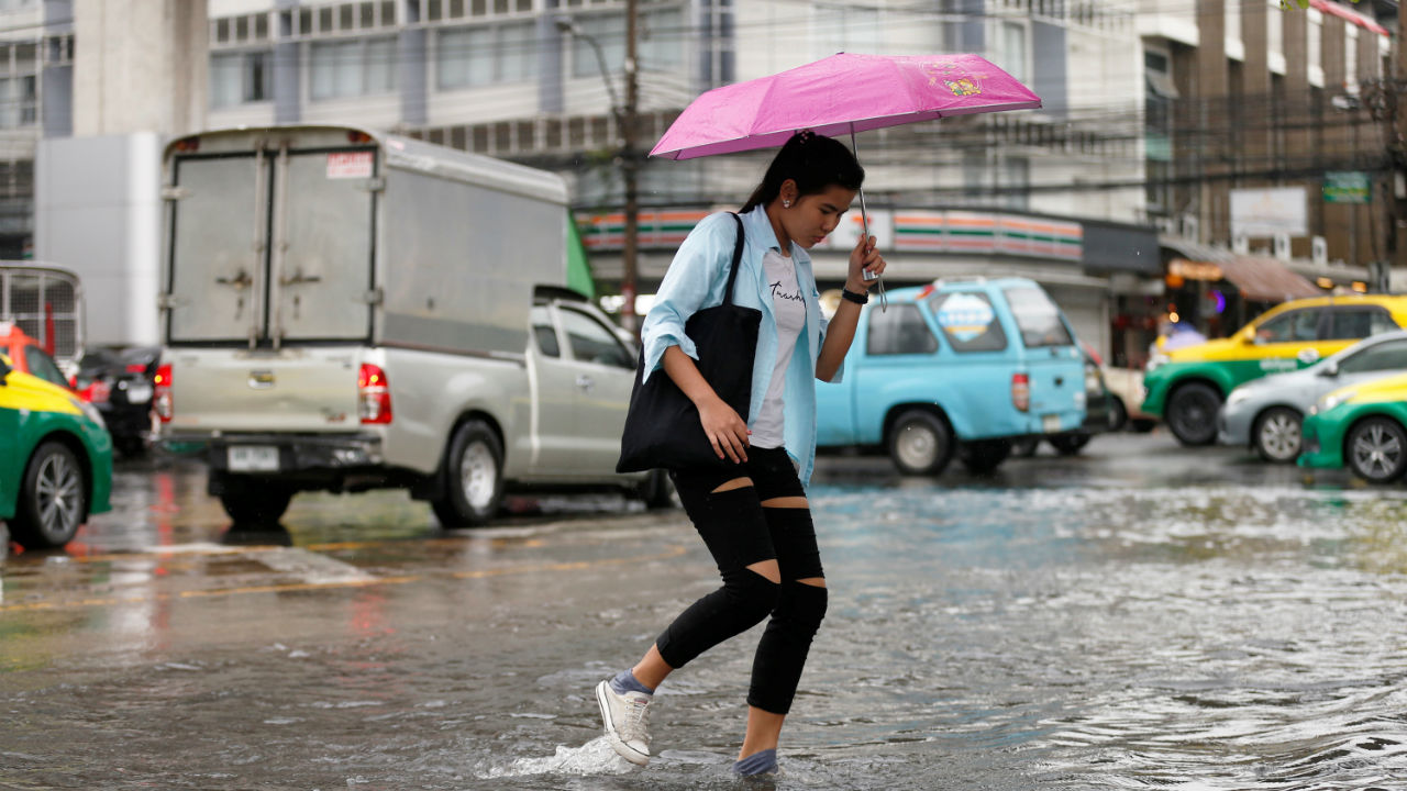A woman walks on a flooded street in Bangkok, Thailand. (Image: Reuters)