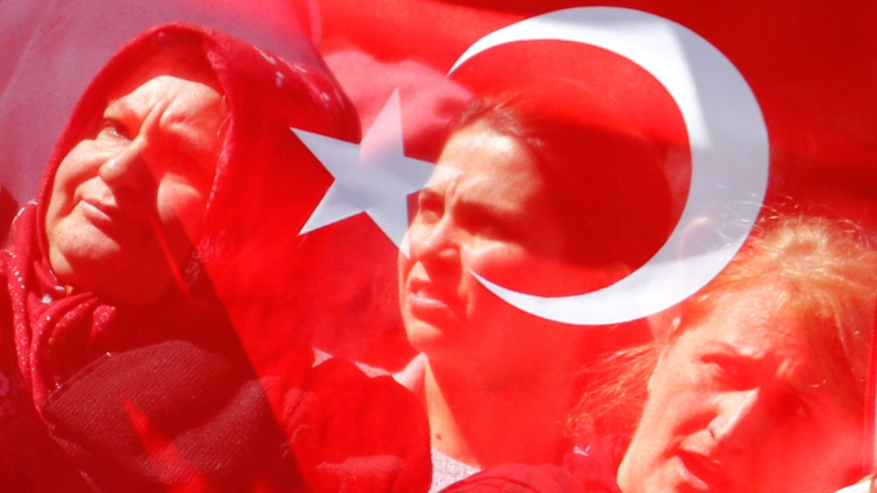 Supporters of Turkish President Tayyip Erdogan are seen through Turkish flags as they await Erdogan's arrival in Berlin near the Adlon Hotel in Berlin, Germany. (Reuters)