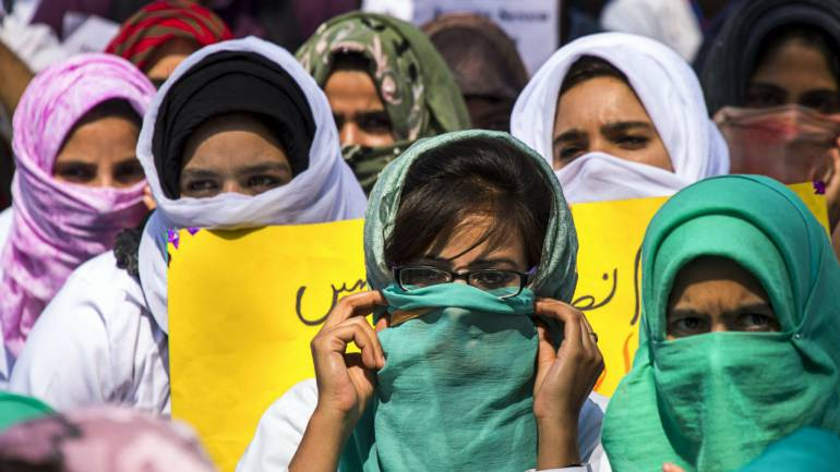 Students of Sher-e-Kashmir Institute of Medical Science (SKIMS) Soura, display placards during a silent protest, demanding the release of their colleague Mohammad Iqbal who was arrested by police in Jhajjar Kotli incident last week, in Srinagar, Jammu and Kashmir. (Image: PTI)