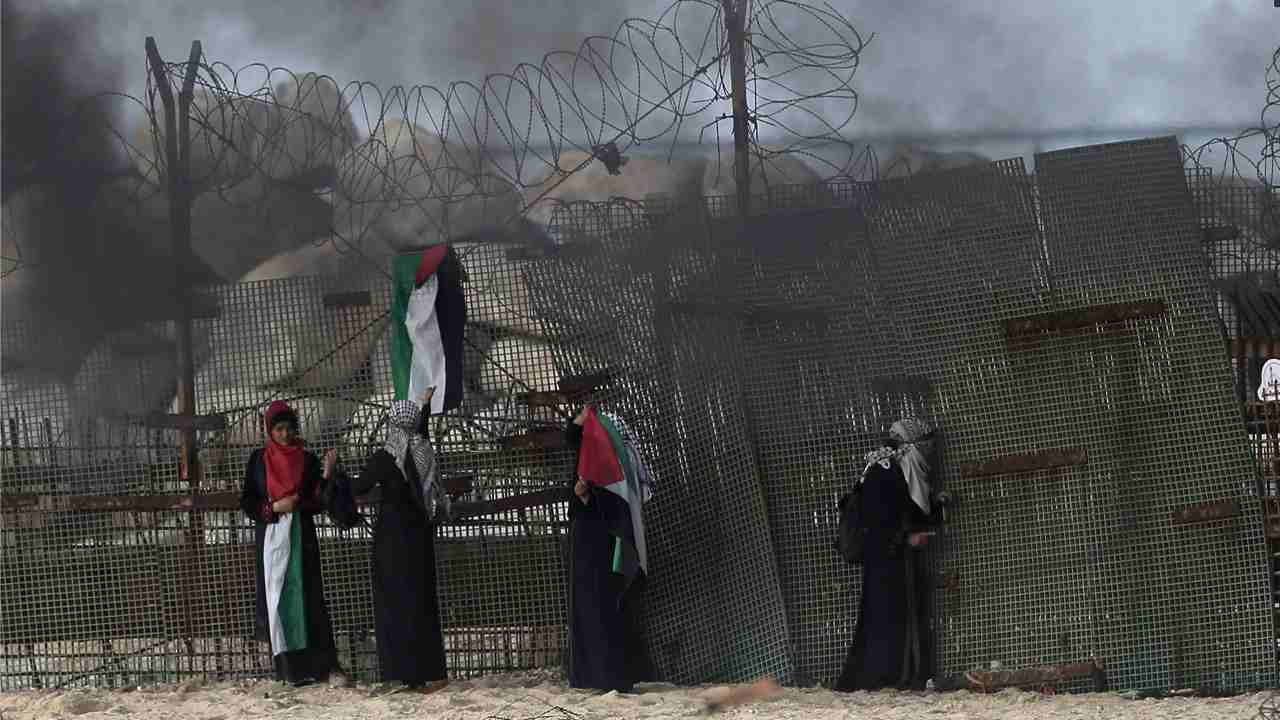 Palestinian protesters hide behind the border fence during a protest on the beach at the border with Israel near Beit Lahiya, northern Gaza Strip. AP/PTI)