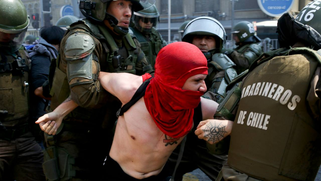 A protester is detained by police during a march against the commemoration of the discovery of the Americas, organized by indigenous groups demanding autonomy and the recovery of ancestral land, in Santiago, Chile (Image: AP/PTI)