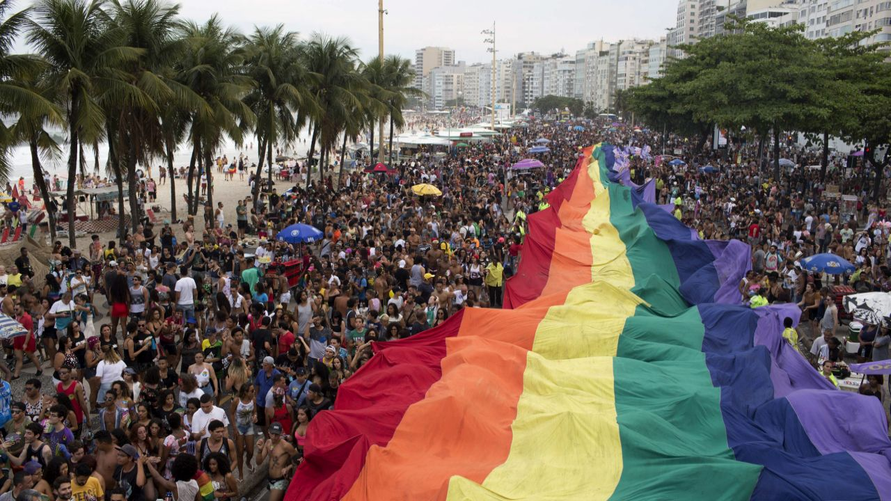 """People carry a giant gay pride flag during the annual Gay Pride Parade along Copacabana beach in Rio de Janeiro, Brazil. One week before Brazil's presidential elections, organizers coined the theme of the parade """"Vote in ideas and not in people,"""" aiming to encourage people to vote for candidates who support gay and human rights. (AP/PTI)"""
