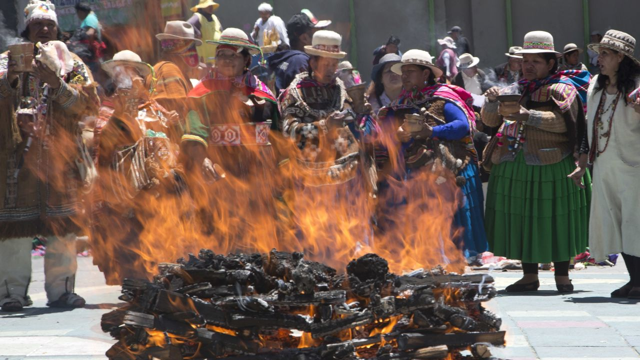 """Aymara priests burn sweets as offerings in honor of mother earth, known as the """"Pachamama,"""" the day before the International Court of Justice in The Hague rules on Bolivia's demand for Chile to enter into talks regarding granting the landlocked country access to the Pacific Ocean, outside the Basilica of San Francisco in La Paz, Bolivia. The country lost its only seacoast to neighboring Chile during a war from 1879 to 1883 and the nation has demanded ocean access for generations. (AP/PTI)"""