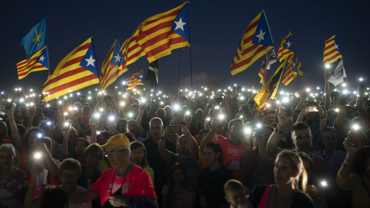 """Pro independence demonstrators wave """"esteladas"""" or independence flags, as they sing in a field overlooking the Lledoners prison in Sant Joan de Vilatorrada, about 50 kilometres away from Barcelona, Spain. Hundreds of Catalonia residents gathered near the Lledoners prison, where most prominent jailed separatists are awaiting trial, to mark nearly one-year since an unauthorized independence referendum was held in this region of Spain last year. (AP/PTI)"""