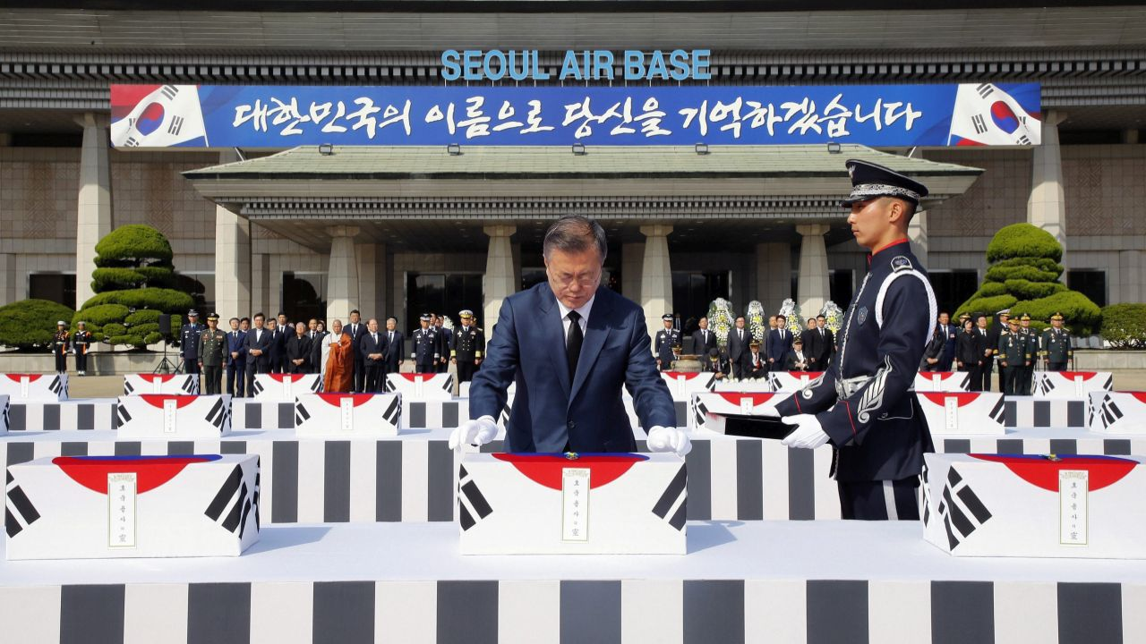 """South Korean President Moon Jae-in, center, puts war medals on the remains of 64 South Korean soldiers killed in North Korea during the Korean War, which arrived at Seoul Air Base in Seongnam, South Korea, from Hawaii. They were earlier found in North Korea during a joint 1996-2005 excavation project between the United States and North Korea before forensic identification tests in Hawaii confirmed they belong to South Korean war dead, according to Seoul's Defense Ministry. The sign reads """" We will remember you in the name of the Republic of Korea."""" (AP/PTI)"""