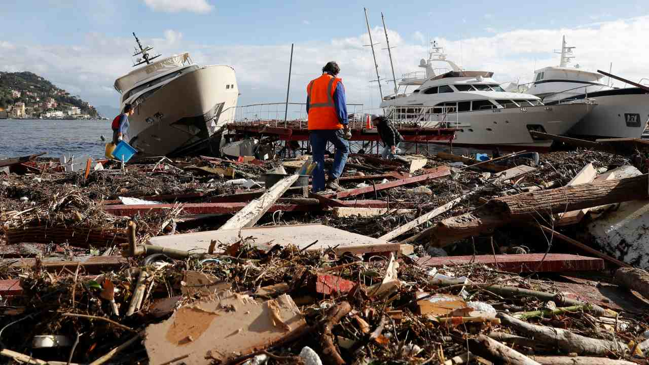 People clean up debris of yachts and boats which were washed ashore, a day after a storm, in Rapallo, northern Italy.(Image: AP/PTI)