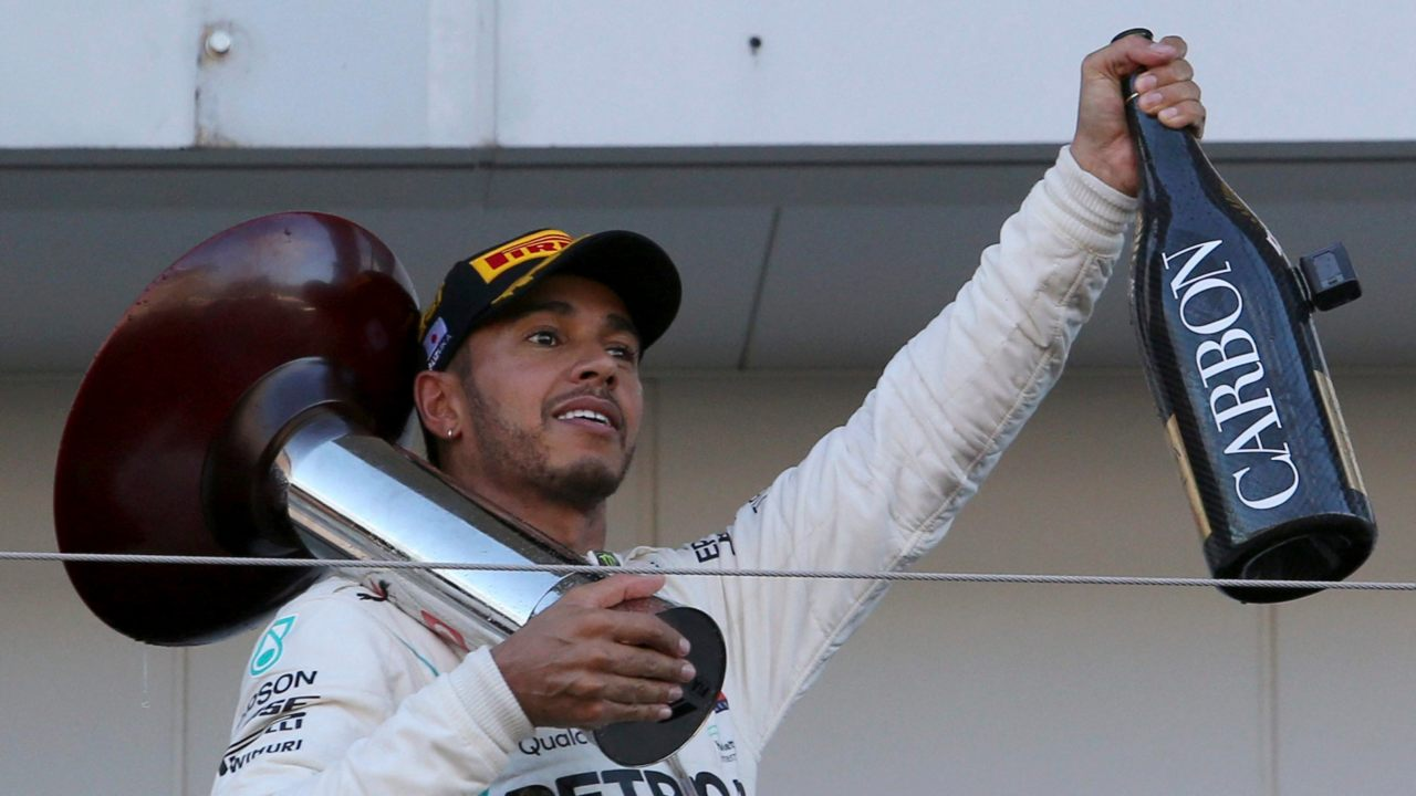 Mercedes driver Lewis Hamilton of Britain holds his trophy and a bottle of champagne on the podium after winning the Japanese Formula One Grand Prix at the Suzuka Circuit in Suzuka, central Japan. (Image: AP/PTI)