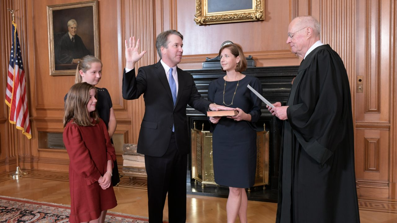 Chief Justice John Roberts, right, administers the Constitutional Oath to Judge Brett Kavanaugh in the Justices' Conference Room of the Supreme Court Building. Ashley Kavanaugh holds the Bible. In the foreground are their daughters, Margaret, left, and Liza. (Image: AP)