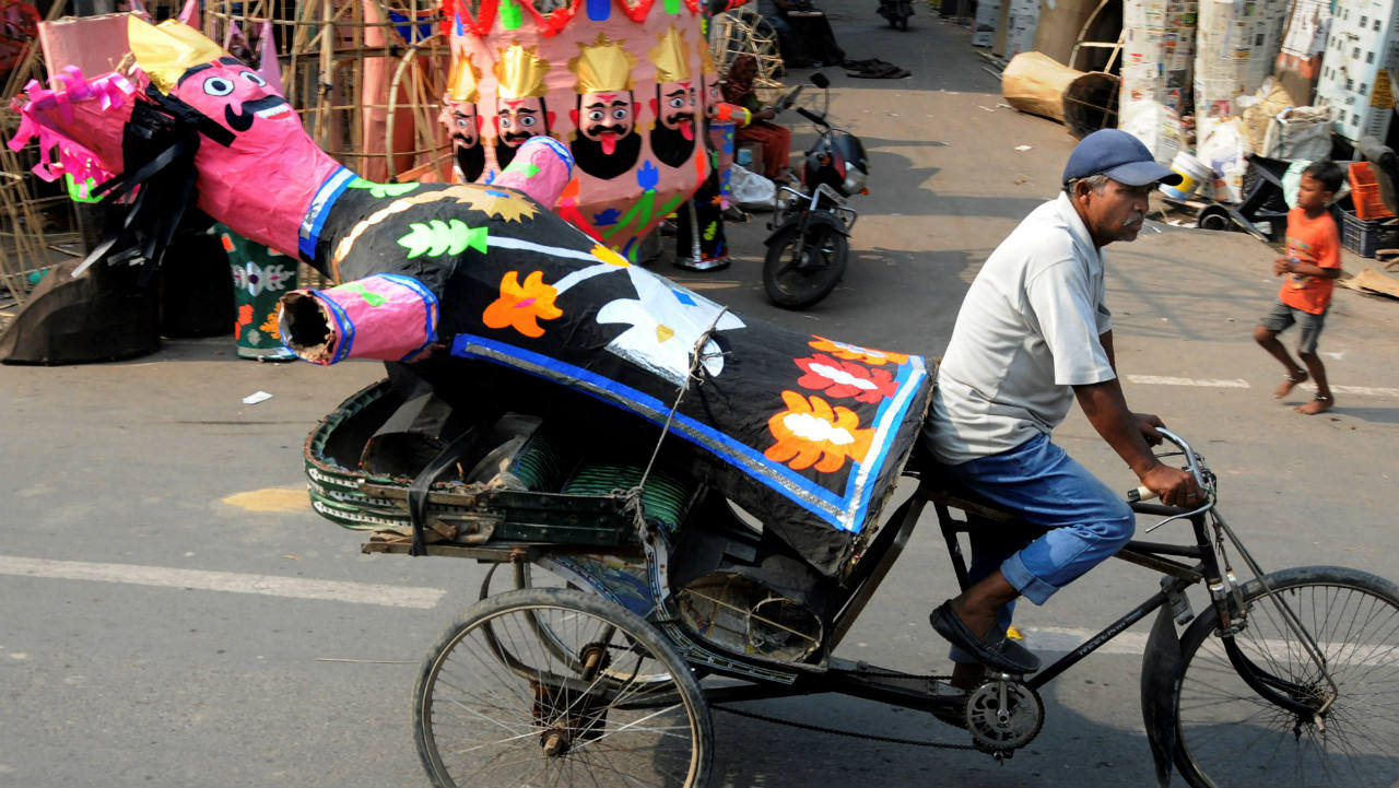 A rickshaw puller carries an effigy of demon-king Ravana for installation ahead of Dussehra festival, in Amritsar. (Image: PTI)