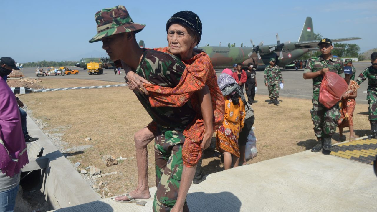 An Indonesian soldier carries an elderly woman evacuated after an earthquake and tsunami hit Palu at Hasanuddin Airport in Makassar, South Sulawesi, Indonesia. (Reuters)