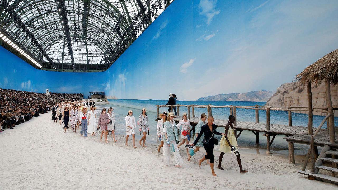 Models present creations by German designer Karl Lagerfeld as part of his Spring/Summer 2019 women's ready-to-wear collection show for fashion house Chanel at the Grand Palais transformed as a beach scene during Paris Fashion Week in Paris, France. (Image: Reuters)