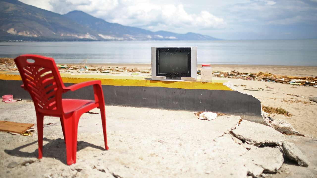 A red plastic chair and a television are pictured on the beach in Palu, Central Sulawesi, Indonesia. (REUTERS)