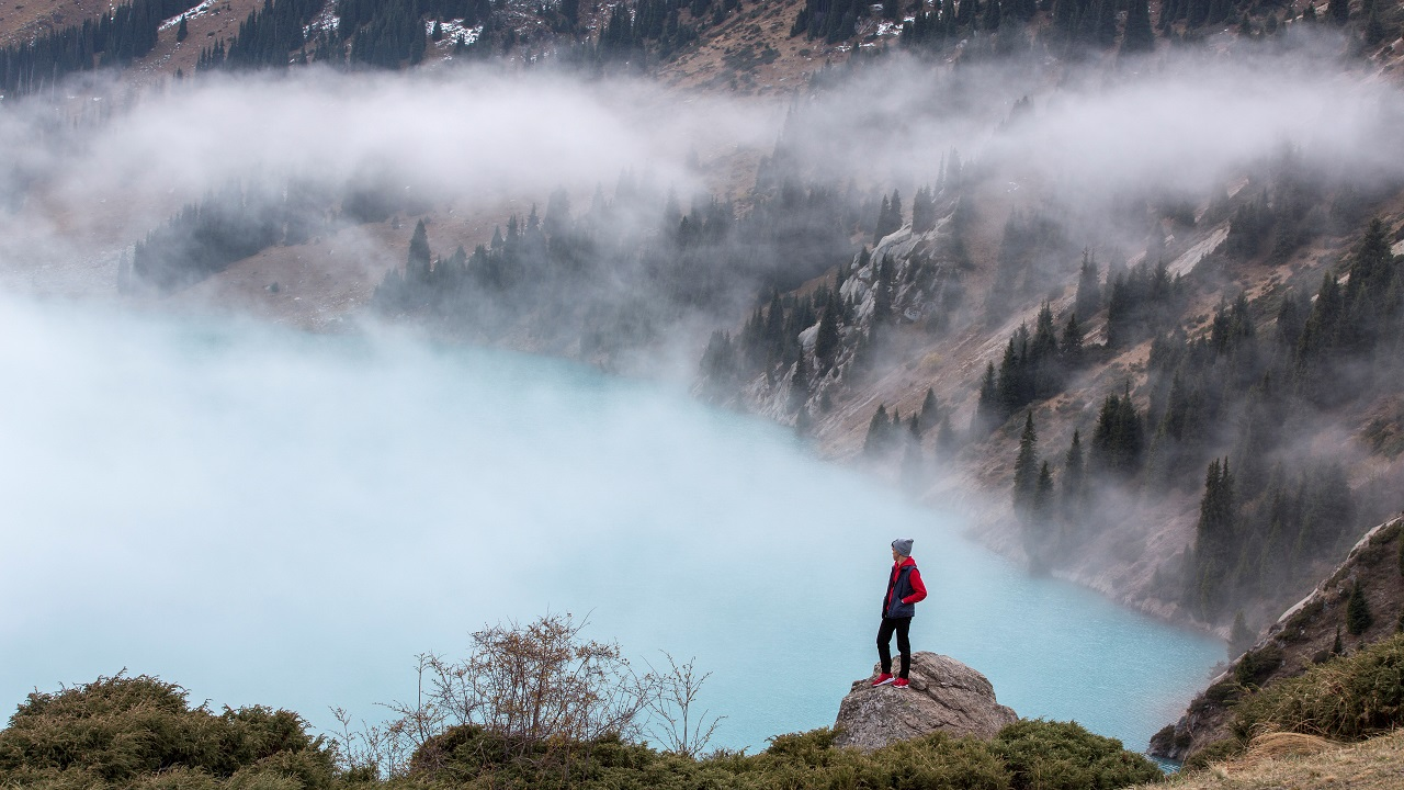 A man stands on a rock while looking at the Big Almaty Lake in the mountainous area outside Almaty, Kazakhstan. (Image:Reuters)