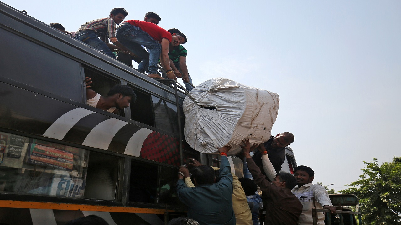 Migrant workers from Madhya Pradesh and Uttar Pradesh load their luggage on the roof of a bus as they prepare to depart, in Ahmedabad. (Image:Reuters)