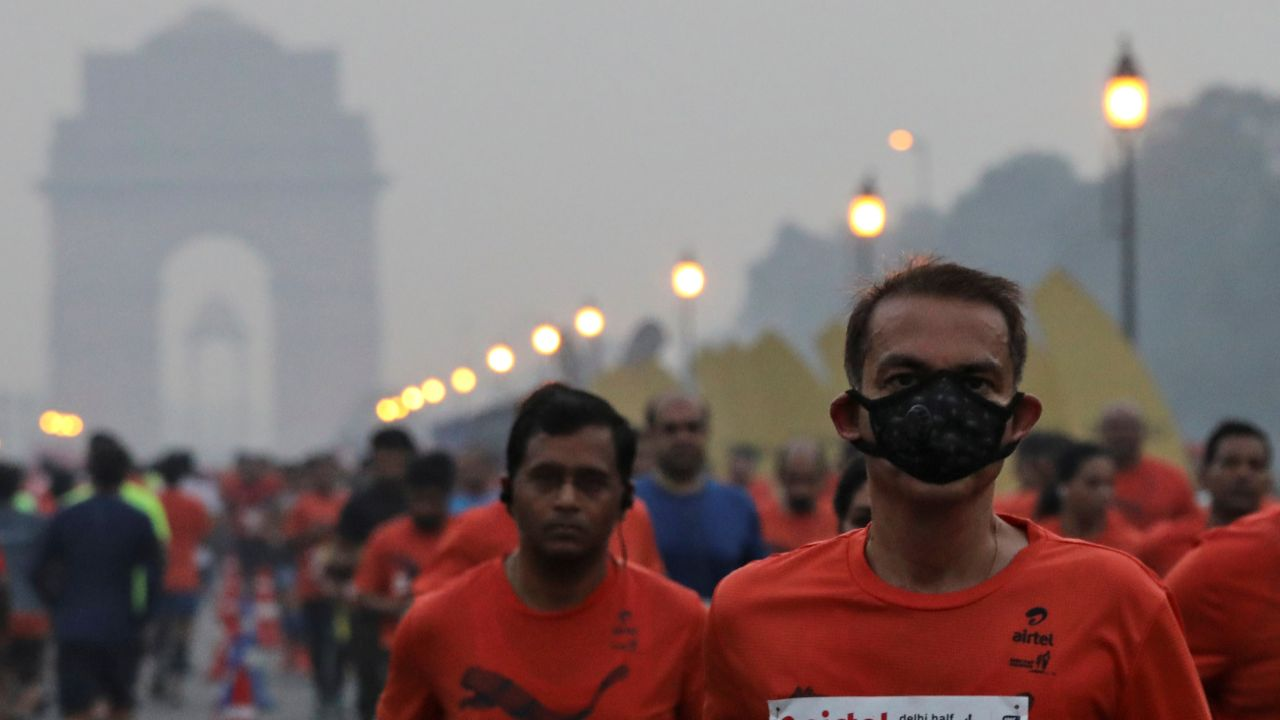 A runner wearing a face mask for protection from air pollution takes part in the Airtel Delhi Half Marathon in New Delhi. (Reuters)