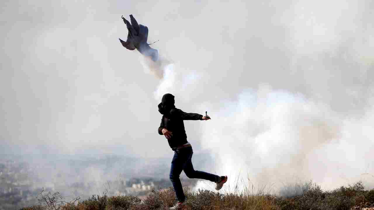 A Palestinian demonstrator hurls back a tear gas canister fired by Israeli troops during a protest against Israeli land seizures for Jewish settlements, in the village of Ras Karkar, near Ramallah in the occupied West Bank. (Reuters)