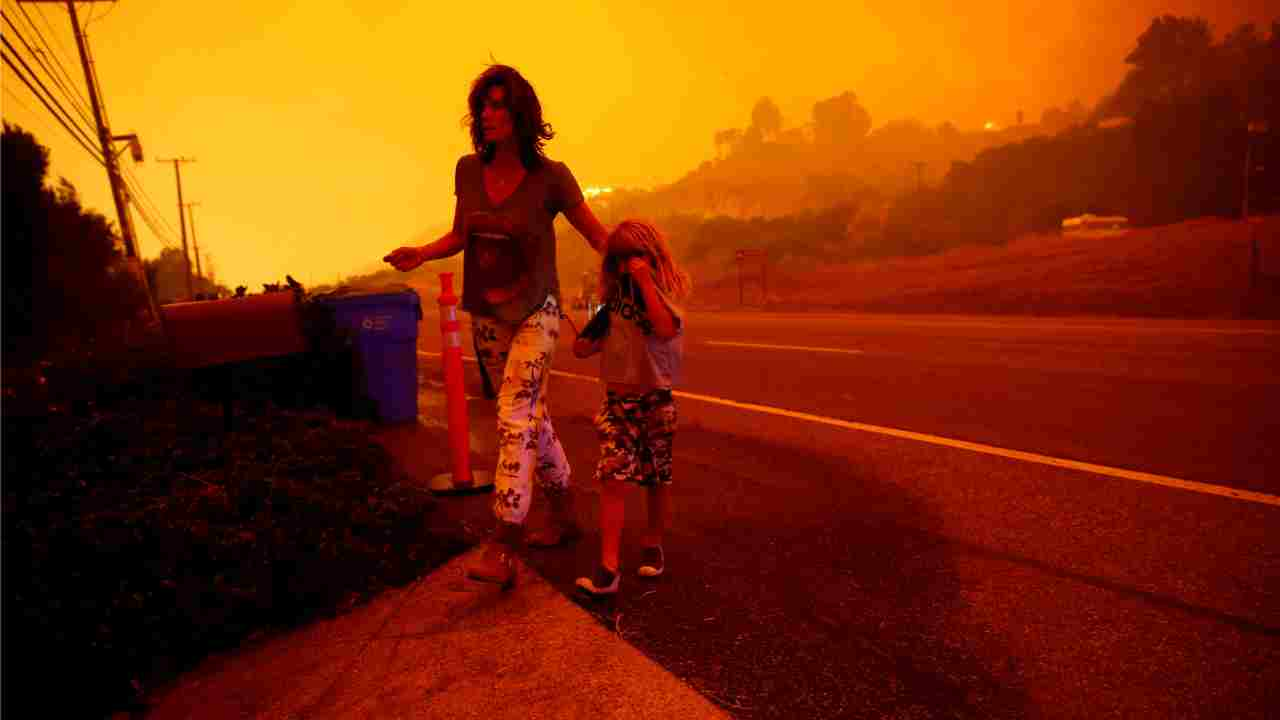 Gabi and Jonah Frank walk on Pacific Coast Highway as the Woolsey Fire threatens their home in Malibu, California, US. The fire destroyed dozens of structures, forced thousands of evacuations and closed a major freeway. (Reuters)