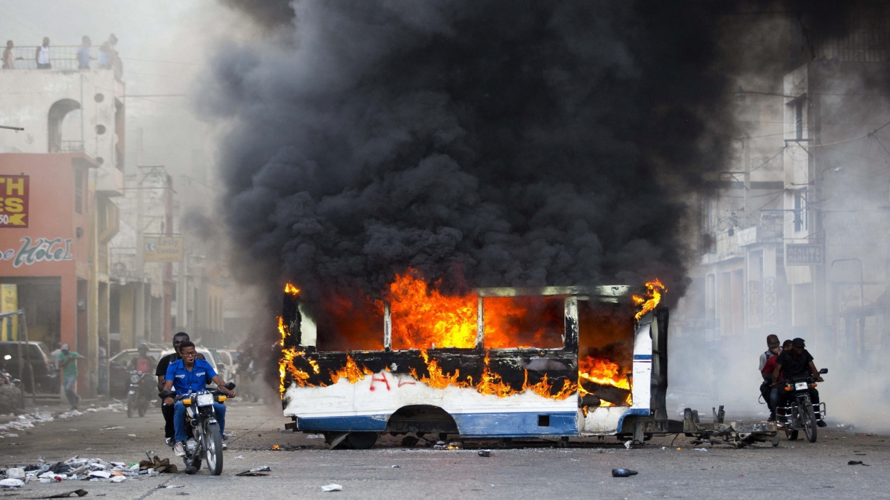 Motorcyclists pass a burning bus, set fire by opposition protesters demanding to know how Petro Caribe funds have been used by the current and past administrations, on the sidelines of events marking the 215th anniversary of independence Battle of Vertieres in Port-au-Prince, Haiti, Sunday. (Image Source: PTI)