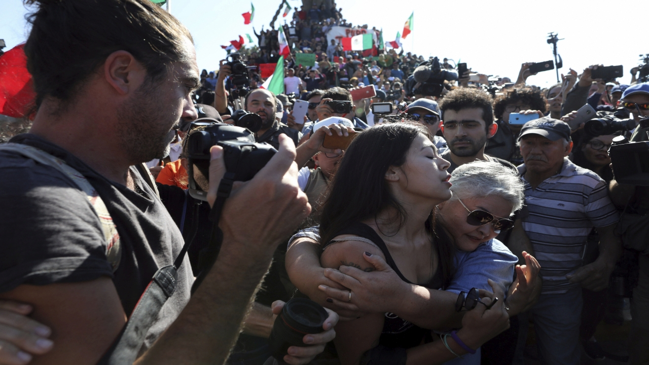 A woman who supports migrants embraces another supporter to help her leave the area so as not to be attacked by demonstrators protesting the presence of thousands of Central American migrants in Tijuana, Mexico, Sunday. Image Source: PTI)