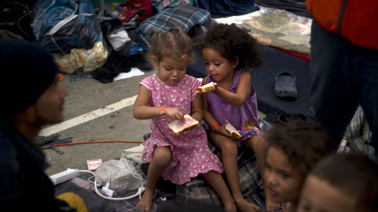Two girls, part of the migrant caravan, share a sandwich at a shelter in Tijuana, Mexico. Migrants camped in Tijuana after traveling in a caravan to reach the US are weighing their options after a US court blocked President Donald Trump's asylum ban for illegal border crossers. (Image: PTI)
