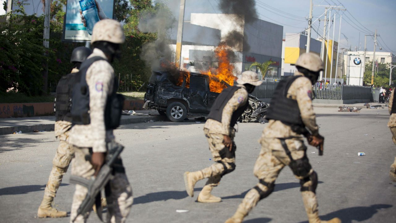 Police officers run past a burning car that was set on fire by protesters after it careened out of control and hit a group of persons in Port-au-Prince, Haiti. (Image: PTI)
