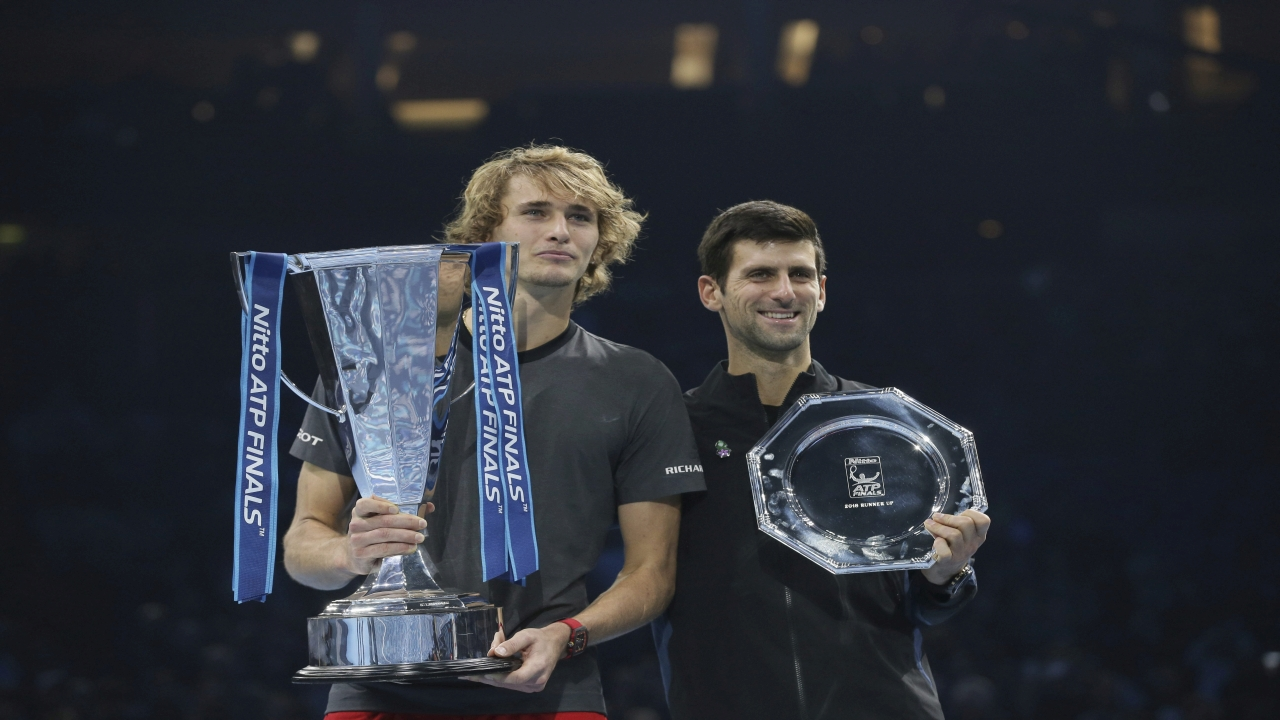 Alexander Zverev of Germany holds his winner trophy and Novak Djokovic of Serbia holds his runner-up trophy after their ATP World Tour Finals singles final tennis match at the O2 Arena in London, Sunday. (Image Source: PTI)
