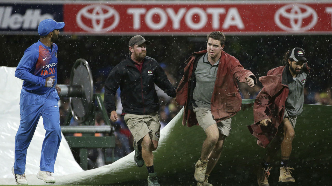 Groundsmen were pressed into action as the heavens opened up during the course of 17th over. Heavy rains stopped the action for considerable time and the match was curtailed to a 17-over affair. (Image: AP)