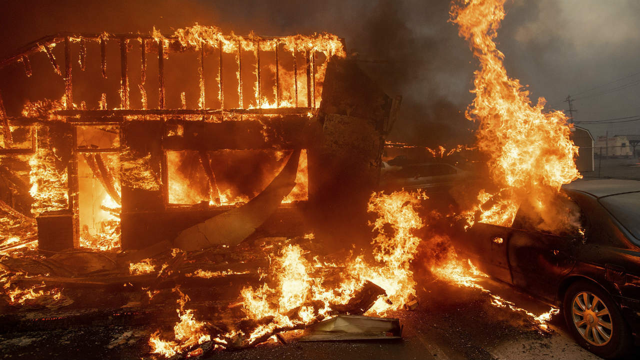 Flames consume a car and building as the Camp Fire tears through Paradise, California, US. (Image: AP)