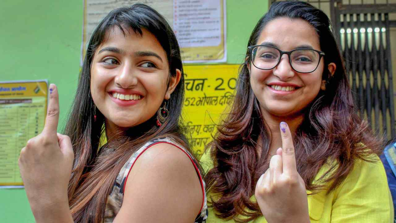 First-time voters show their fingers marked with indelible ink after casting votes for the assembly elections, at a polling station in Bhopal. (Image: PTI)