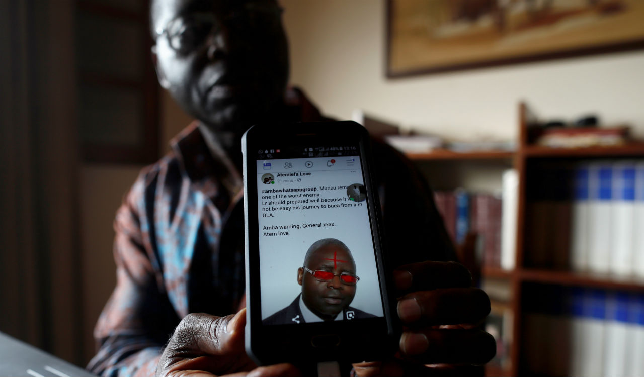 Simon Munzu, a former UN official, who is campaigning for peace in the Anglophone regions of Cameroon, shows a threat message posted against him on social media by separatists during an interview with Reuters. (Image: Reuters)