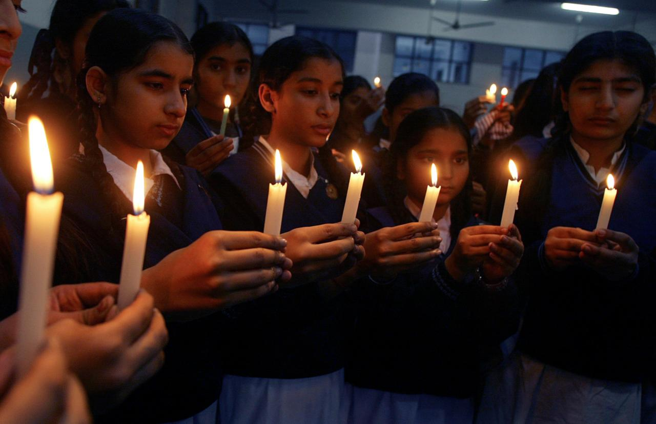 Students hold candles during a vigil for the victims of the Mumbai attacks at a school. (Image: Reuters)
