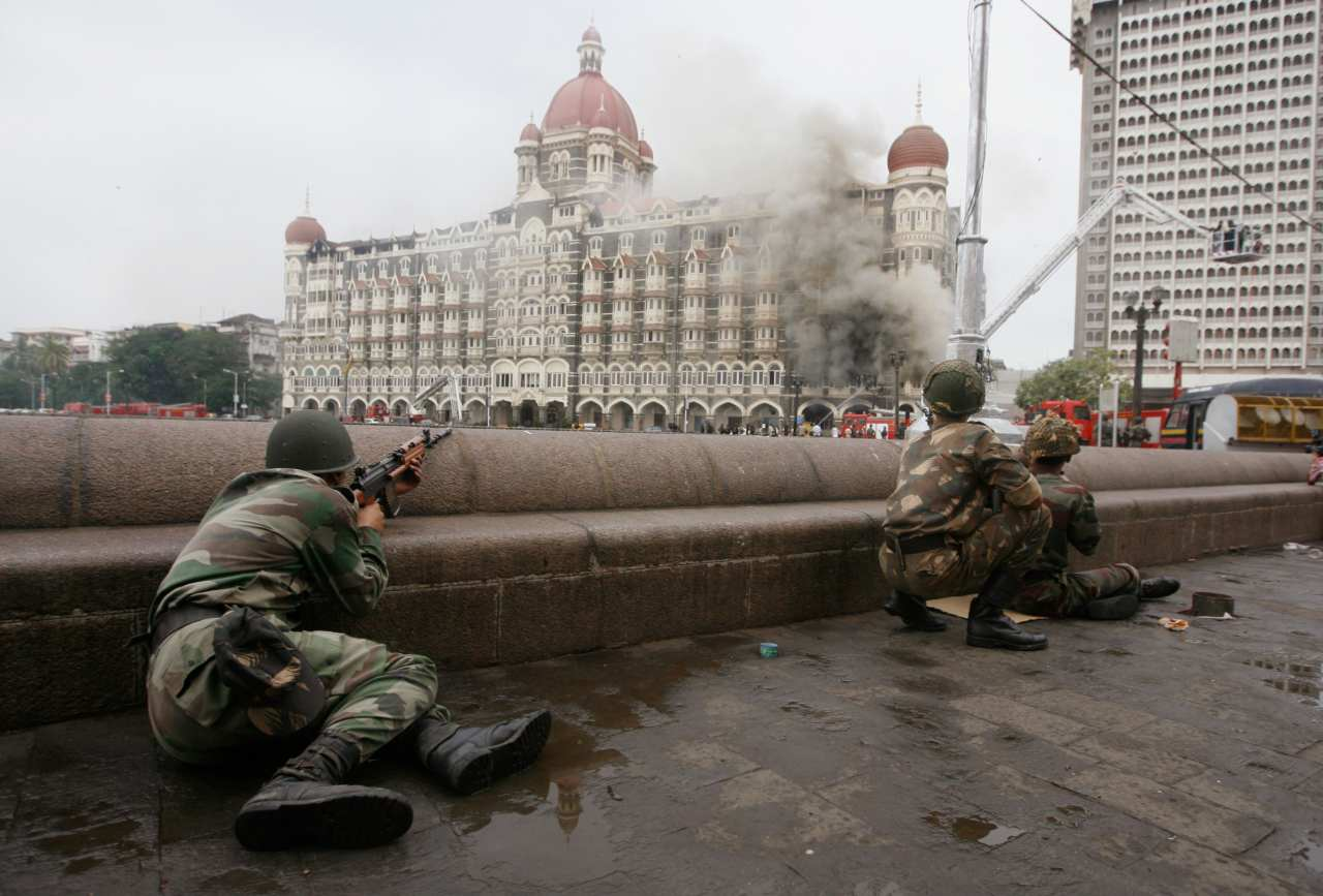 Military personnel take position as terrorists hurl bombs at the Taj Mahal Palace Hotel (seen in the background) in Mumbai on November 29, 2008. (Image: Reuters)