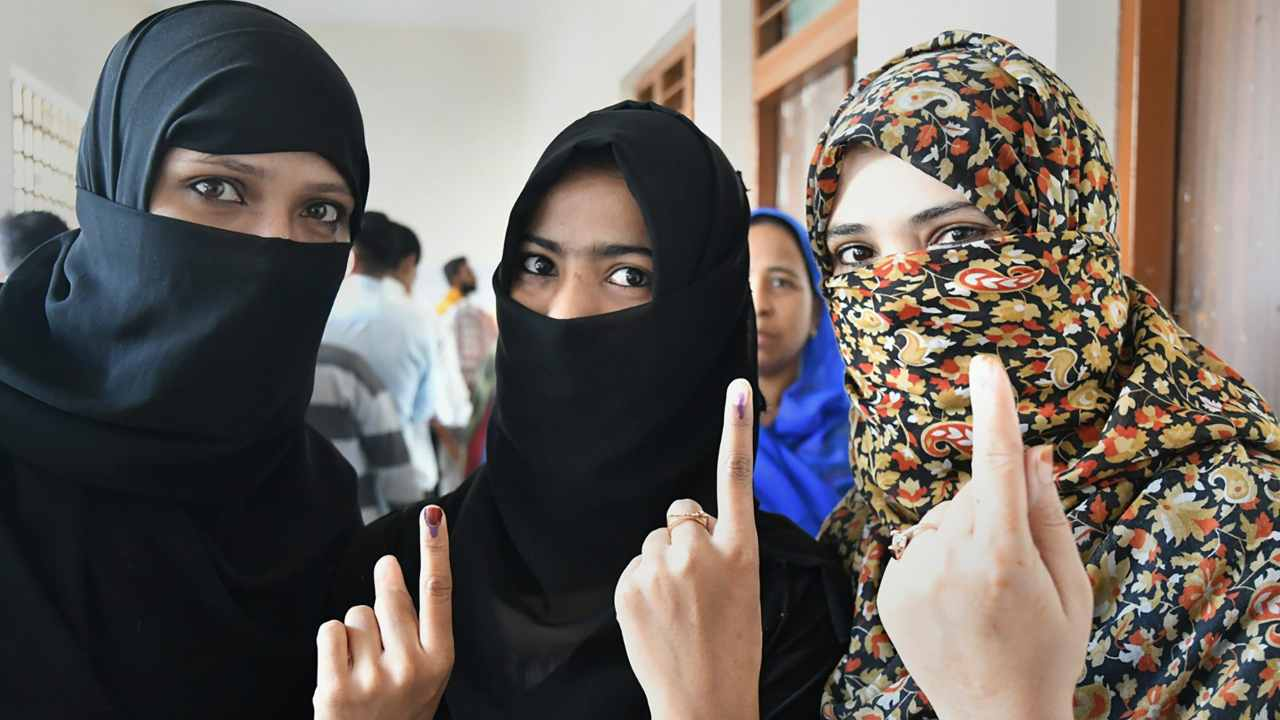 Muslim women show their fingers marked with indelible ink after casting votes for Assembly elections, outside a polling station in Bhopal. (Image: PTI)