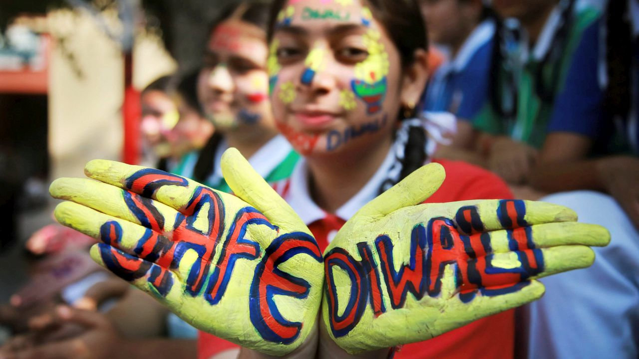 A student displays a message painted on her hands to create awareness regarding the hazardous effects of air pollution during 'Diwali', festival, in Jammu. (PTI)