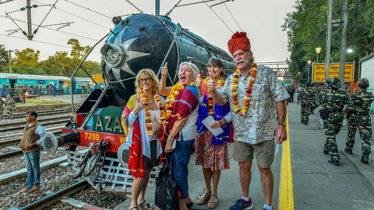 Tourists pose for photos in front of the luxury train 'Palace on Wheels' which starts its 12th tour, from Safdarjung Railway Station in New Delhi. (Image: PTI)