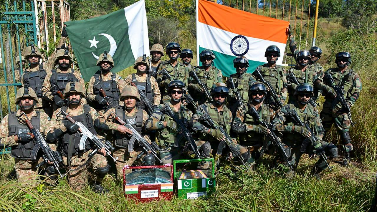 Indian and Pakistani army men pose for a group photograph after exchanging sweets on the occasion of Diwali festival, in Poonch. (Image: PTI)