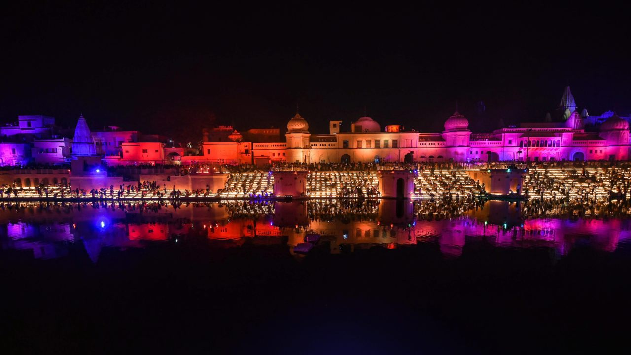People light earthen lamps on the banks of River Saryu during Deepotsav (grand Diwali celebrations) in Ayodhya. (Image: PTI)