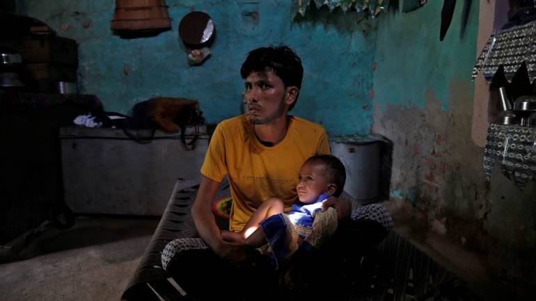 Azmat, 27, recovers on a charpaai with his son at his home in Jaisinghpur. He survived an attack by cow vigilantes when transporting cattle which left Pehlu Khan dead. (Image: Reuters)