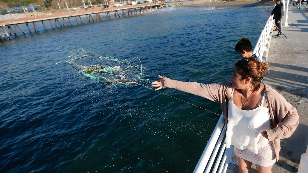 A woman casts a net to catch fish on a dock at a fishermen's market in Valparaiso. (Image: Reuters)