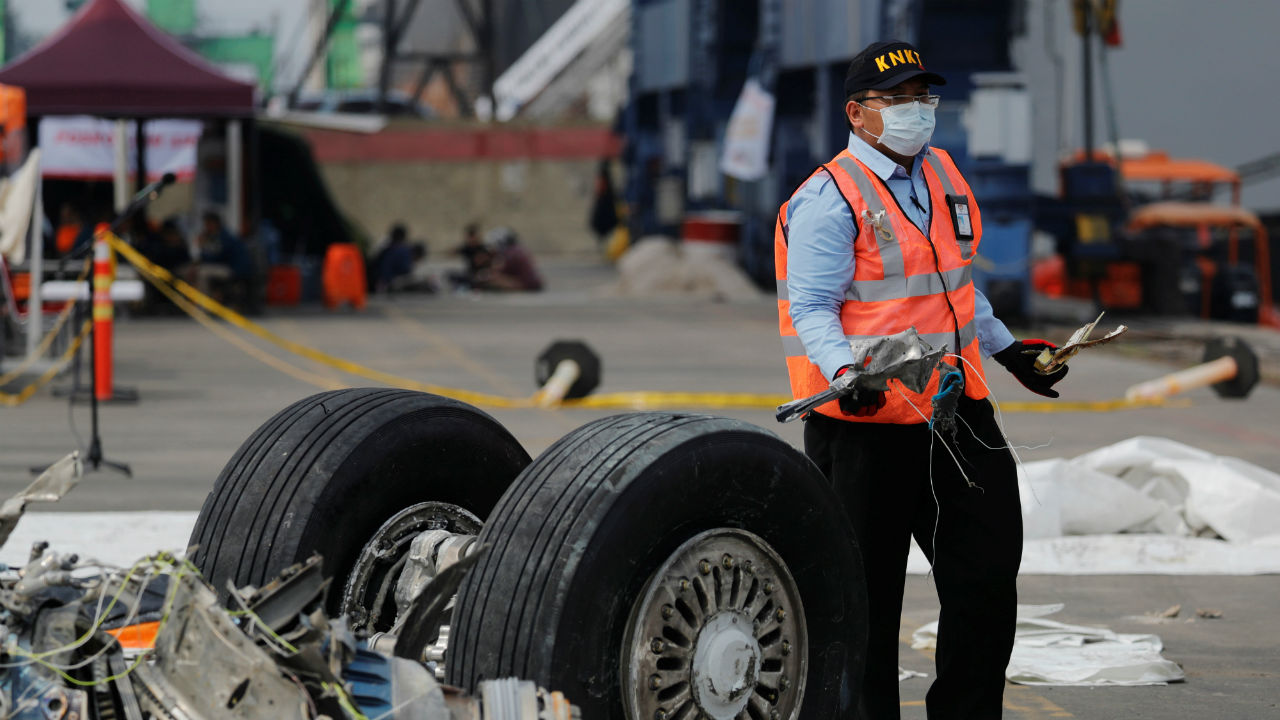 An Indonesian National Transportation Safety Commission (KNKT) official carries debris from the crashed Lion Air flight JT610 at Tanjung Priok port in Jakarta, Indonesia. (Image: Reuters)