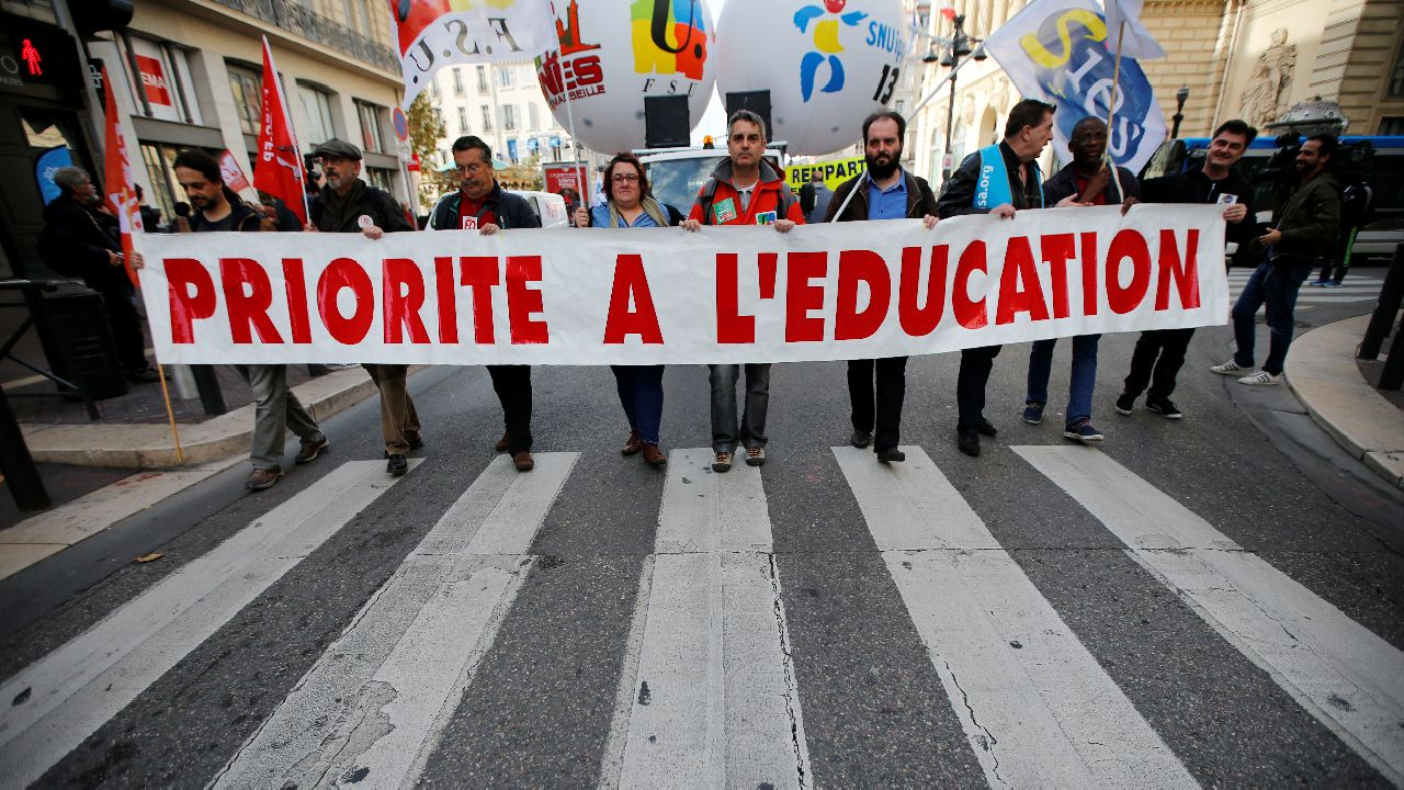 """French teachers hold a banner which reads """"Priority to education"""" as they attend a demonstration against the French government's reform plan in Marseille. (Image source: Reuters)"""