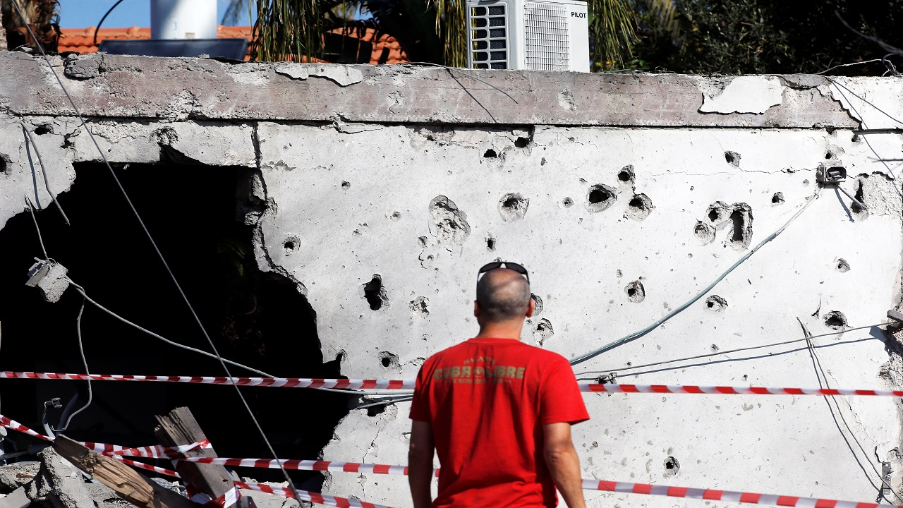 A man stands inside a house damaged by a rocket fired from the Gaza Strip overnight, in the Israeli city of Ashkelon (Image:Reuters)