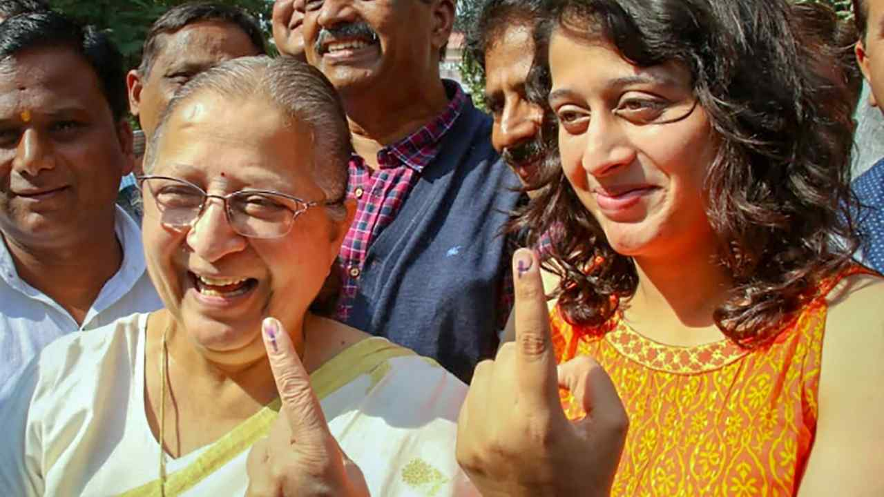 Lok Sabha Speaker Sumitra Mahajan, along with her grand-daughter, shows her finger marked with indelible ink after casting her vote in Indore. (Image: PTI)