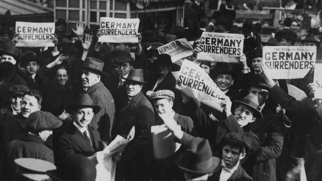 Pictured: People gathered at Times Square, holding copies of newspapers with a headline about the signing of the Armistice to end the war. (Image: Reuters)