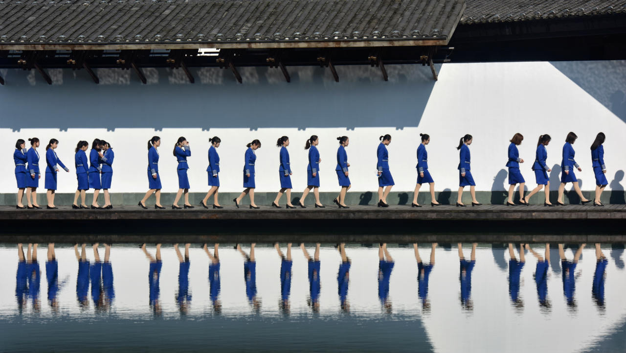 Attendants for the fifth World Internet Conference (WIC) are seen reflected in the water during a group photo session outside the venue, in Wuzhen town of Jiaxing, Zhejiang province, China. (Image: Reuters)