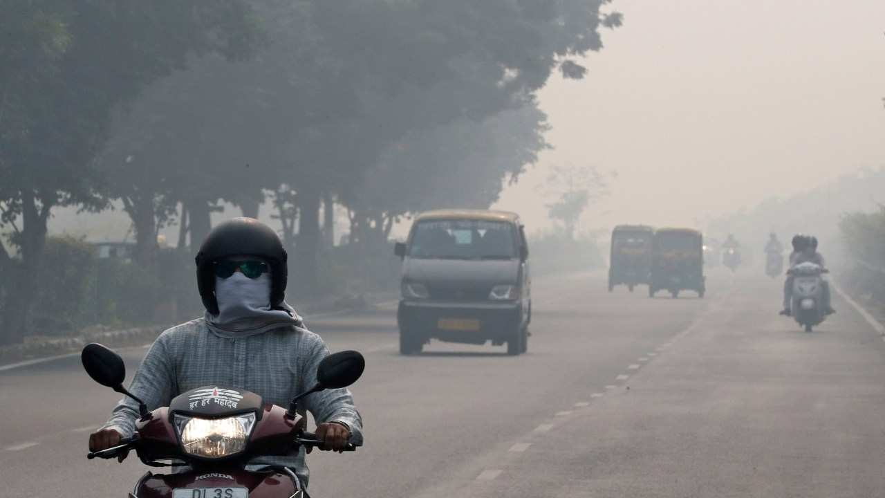 People commute on a smoggy morning in New Delhi on November 5 (REUTERS)