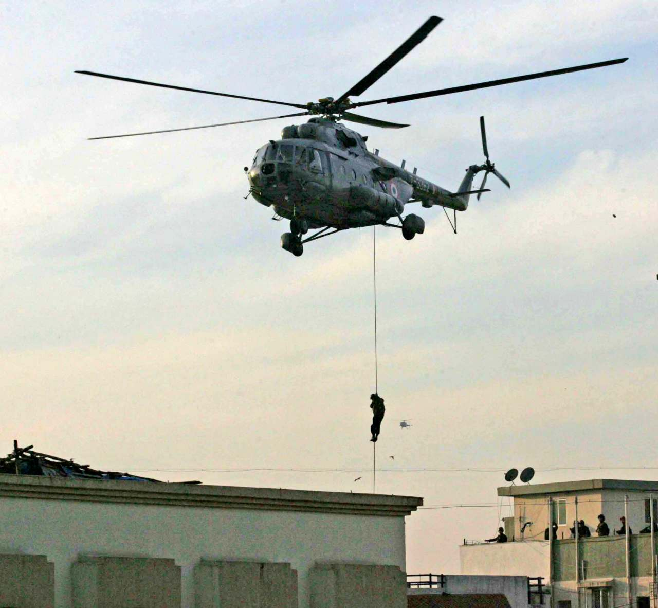 Pictured:- A National Security Guard (NSG) commando rappels from a helicopter near Nariman House where suspected militants were believed to be hiding. (Image: Reuters)